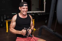 Man trains in the gym with weights. young guy doing exercises for good muscles. Fitness personal trainer working. Sports motivatio stock photo