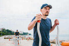 A man trains on sporting equipment in a city in the open air. The concept of a healthy lifestyle and accessibility of. Sports training for every person Royalty Free Stock Image