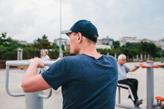 A man trains on sporting equipment in a city in the open air. The concept of a healthy lifestyle and accessibility of. Sports training for every person Royalty Free Stock Photos