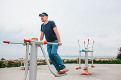 A man trains on sporting equipment in a city in the open air. The concept of a healthy lifestyle and accessibility of Stock Photography