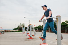 A man trains on sporting equipment in a city in the open air. The concept of a healthy lifestyle and accessibility of Stock Photos