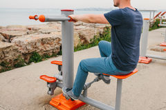 A man trains on sporting equipment in a city in the open air. The concept of a healthy lifestyle and accessibility of. Sports training for every person Royalty Free Stock Photography