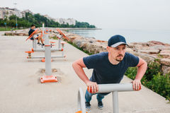 A man trains on sporting equipment in a city in the open air. The concept of a healthy lifestyle and accessibility of. Sports training for every person Royalty Free Stock Images