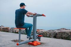 A man trains on sporting equipment in a city in the open air. The concept of a healthy lifestyle and accessibility of. Sports training for every person Stock Photography