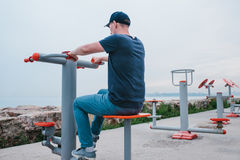A man trains on sporting equipment in a city in the open air. The concept of a healthy lifestyle and accessibility of Stock Photo