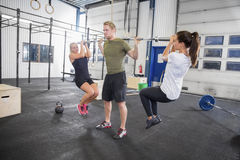 Man trains squats with girls as weights Royalty Free Stock Images