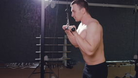 The man trains triceps in the gym stock footage