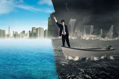 Man transforming collapse city into new city. Businessman standing on a boat while using a roller to change a collapse city into a new city. Concept of an effort royalty free stock photos