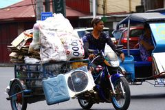 A man transports recyclable materials on a tricycle. Stock Photos