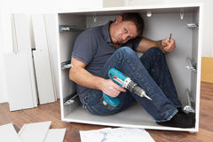 Man Trapped Whilst Assembling Flat Pack Furniture. Looking confused Royalty Free Stock Image