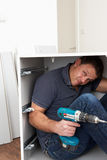 Man Trapped Whilst Assembling Flat Pack Furniture Stock Photo