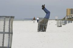 Man in trash can. At beach Royalty Free Stock Image
