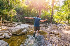 Man travel in the forest and running in to the water stock photo
