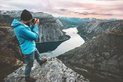 Man travel photographer taking photo landscape in Norway. Mountains standing on cliff hobby lifestyle adventure vacations lake aerial view stock photo
