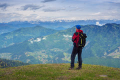Man traveler admires a panorama of mountains Royalty Free Stock Image