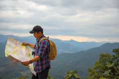 Man traveler with backpack checks map to find directions. In wilderness area Royalty Free Stock Photos