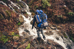 Man Traveler with backpack crossing waterfall Stock Photography
