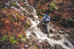 Man Traveler with backpack crossing waterfall Stock Images