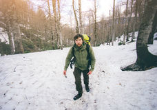 Man Traveler with backpack hiking in snow forest Royalty Free Stock Image