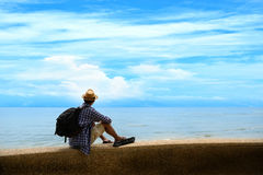 Man traveler with backpack relaxing at seaside Royalty Free Stock Photo