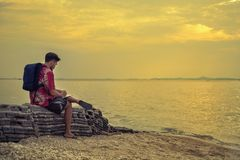 Man traveler with backpack on the rocks near the sea at sunset a. Nd looking at the note book, Lifestyle concept vacations outdoor solitude emotions aerial view Royalty Free Stock Photos