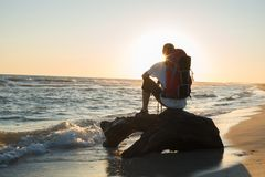 Man traveler with backpack sits in the surf. Man traveler with backpack sits on a snag in the surf, in the rays of setting sun and admires the sea. Amazing Royalty Free Stock Photography