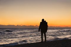 Man traveler with a backpack is standing on the beach Royalty Free Stock Images