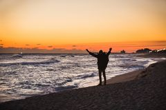 Man traveler with a backpack is standing on the beach Stock Photo