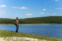 Man traveler with backpack standing near the lake. In the Ural mountains Royalty Free Stock Image
