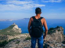 Man traveler with backpack standing on top of a mountain and looking out to the sea. Symbolizes freedom, success and loneliness Stock Photography