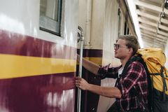 Man traveler with backpack stepping up train at railway station. Male backpacker travel alone. Journey on holiday Stock Image