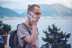 Man traveler with backpack talking on the phone on background of the city. The concept of connection and communication in the journey, roaming Royalty Free Stock Image