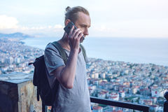 Man traveler with backpack talking on the phone on background of the city. The concept of connection and communication in the journey, roaming Stock Photos