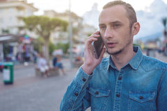 Man traveler with backpack talking on the phone in the background of the street. The concept of connection and communication in the journey, roaming Royalty Free Stock Images