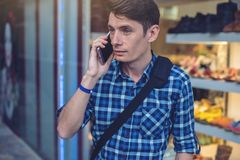 Man traveler with backpack talking on the phone in the background of the street. The concept of connection and communication in the journey, roaming Stock Photography