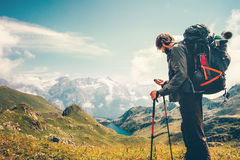 Man Traveler backpacker with gps navigator tracker. Looking for coordinates Travel Lifestyle concept mountains and lake on background survival adventure Stock Image