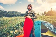 Man Traveler bearded preparing camping equipment mattress and tent outdoor Royalty Free Stock Photos