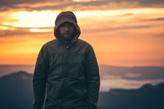 Man Traveler bearded standing alone outdoor. With sunset mountains on background Travel Lifestyle and survival concept Stock Images