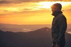 Man Traveler bearded standing alone outdoor. With sunset mountains on background Travel Lifestyle and survival concept Stock Photo