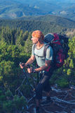 Man traveler with big backpack climbs along the slope Stock Image