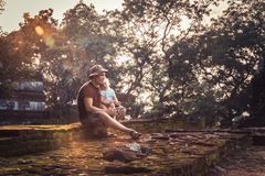 Man traveler with child daughter resting together on ruins at sunset during vacation concept travelling lifestyle stock photos