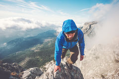 Man Traveler climbing on mountain summit over clouds Stock Image