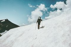 Man Traveler climbing to summit snowy mountains landscape Travel Lifestyle Royalty Free Stock Images