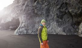 Man walking on Kirkjufjara black sand beach, southern Iceland. Man traveler in colorfull waterproof clothes walking on Kirkjufjara black sand beach, southern Royalty Free Stock Photos