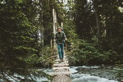 Man Traveler crossing river on log bridge outdoor royalty free stock images