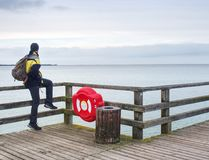 Man traveler with green backpack sit on wooden sea pier. Man in trekking suit Royalty Free Stock Photography
