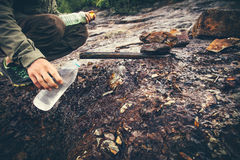 Man Traveler hand taking water in bottle from mineral well Royalty Free Stock Photography