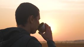 Man traveler hands holding cup of tea or coffee. wonderful morning hot drink on a journey. Adventure, travel, tourism. And camping concept stock video