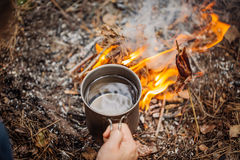 Man traveler hands holding mug with water near the fire outdoors. Bushcraft, adventure, travel, tourism and camping concept royalty free stock photos