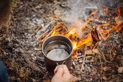 Man traveler hands holding mug with water near the fire outdoors. Bushcraft, adventure, travel, tourism and camping concept stock image